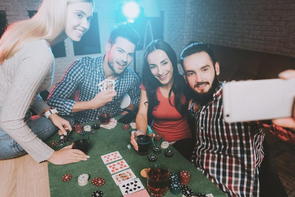 group friends of taking a selfie while enjoying a game of poker