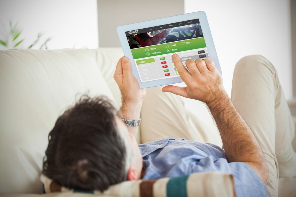 man relaxing on the couch and betting on the football using his tablet